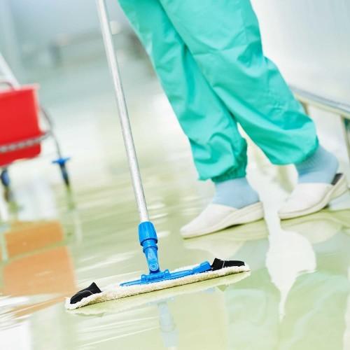 Показана дезинфекция помещения с помощью дезон хлора растворенного уборщиком в зеленых брюках и белых тапочках моющим пол шваброй.