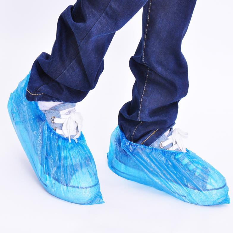 Бахилы одноразовые синего цвета надеты на кроссовки