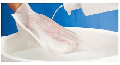 Одноразовые рукавицы для ухода за лежачими больными демонстрация применения, наливается моющее средство на  рукавицу надетую на руку над тазиком с водой.