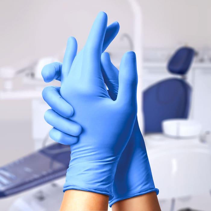 руки в стоматологических перчатках синего цвета перчатках на фоне кабинета