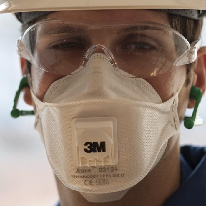 Человек в медицинском респираторе 3м и защитных очках смотрит прямо